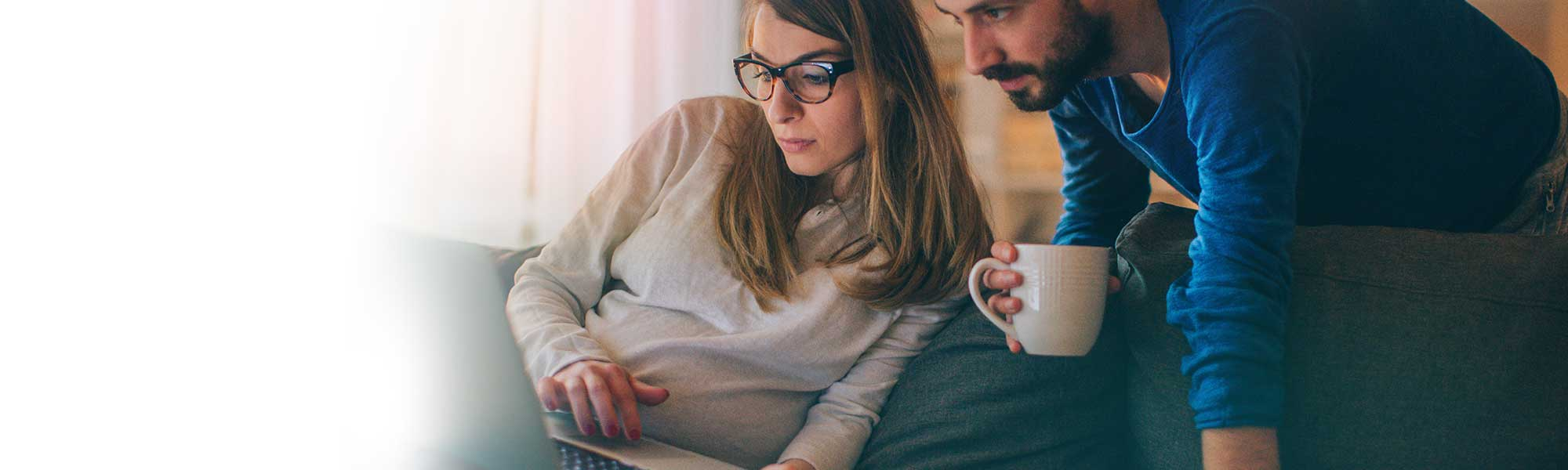 man and woman on couch looking on tablet