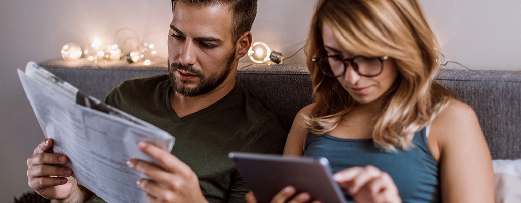 couple looking through newspaper and ipad